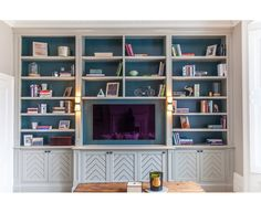 Media Unit / Bookshelf in London Townhouse. Inchyra blue by Farrow and Ball on the back walls. Porta Romana Wall lights.