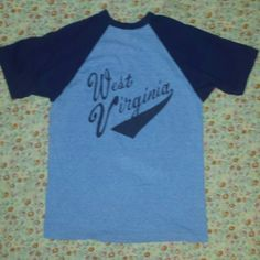 Vintage West Virginia tee This was my sister-in-law's tee when she was a teenager and she graduated in 1986! I found this and a bunch of other vintage tees in my in - law's attic back in 96 and have had them ever since! Thus I'm only the 2nd owner! Super soft, paper thin, great condition, awesome West Virginia graphic, heather blue and cool sleeves! Look at that tag (3rd pic)!! No size but fits S/M best! Hit me up with any questions and thanks for checkin out my vintage awesomeness! Vintage…