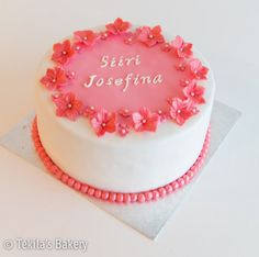 Christening cake with pink flowers and pearls