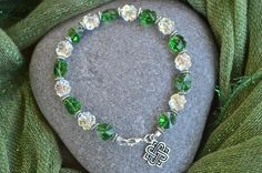 Made from seventeen 8mm Swarovski crystal clovers, this Irish bracelet makes a statement on your wrist. This bracelet is made from real Swarovski crystals, separated with antique silver coiled spacers and clasped with a sterling silver lobster clasp. The Celtic knot charm with interlocked links is also sterling silver.