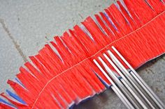 Use red, white and blue crepe paper... stack them and sew down the center. Then use fringe scissors  and snip down one side of the garland or both sides. jh