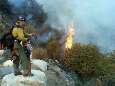 Fireing Out:...  A Granite Mountain Hotshot from Prescott, Arizona monitors a fireing operation in a canyon on the Angeles National Forest during the Station Fire in Los Angeles County, California