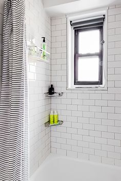 Clinton Hill Co-op bathroom renovation features classic white subway tiles and smart shades for this shower window.