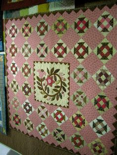 love the pink setting squares with churn dash blocks & center applique!!