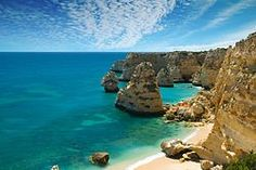 Algarve, Portugal had about 360 days of sun a year. Can be chilly during winter. Portimao is very nice, with both anchoring and marina. Lagos is also nice, but I would have choosen Portimao. About 45 min car ride to Faro International Airport, and a couple of hours to Lisbon.