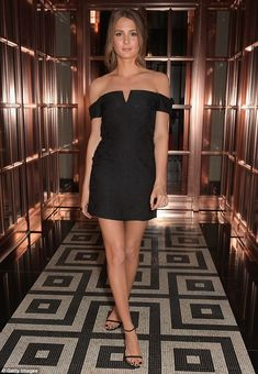 Night out look: Another look saw her spin on the classic little black dress which features off the shoulder arm cuffs and a boned v- notch neckline