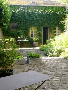 Stone house covered in ivy with cobblestone patio and concrete garden containers. MARIANNE EVENNOU