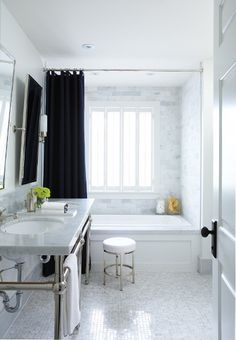 Brillliant Black & White Bathroom      A symphony of white marble creates a rich, polished look.    The double vanity's marble countertop sits on a chunky chrome base and is topped by two tilting mirrors. A black shower curtain grounds the space and provides visual contrast.              Source: House & Home December 2010 issue  Products: Floor tile, marble baseboards, marble vanity top, Moscone Tile; shower wall tile, Ciot; faucets, mirror, wall sconce, sinks, cabinet, tissue holder, vanity…
