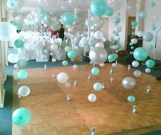 Balloons blown up to different sizes suspended floor to ceiling on fishing line