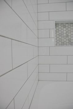 Choosing our shower tile design with subway tile and marble tile niche. This white and gray bathroom features IKEA vanities and herringbone floor. Tile Shower Niche, White Subway Tile Shower, Beveled Subway Tile, Marble Tile Bathroom, Subway Tile Showers, Shower Tile Designs, Diy Bathroom Vanity, Bathroom Floor Tiles, Bathroom Ideas
