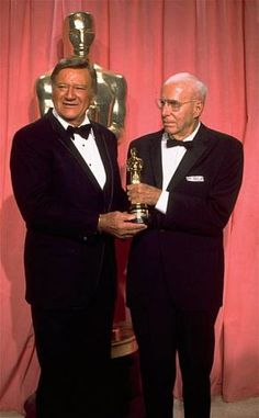 John Wayne, left, presents a special Oscar award to veteran film director Howard Hawks during the 47th Annual Academy Awards ceremony on April 9, 1975 at the L.A. Music Center.  (AP Photo) / SF