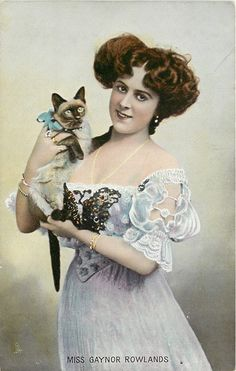 MISS GAYNOR ROWLANDS, stage actress, standing holding Siamese cat postcard.  Tinted