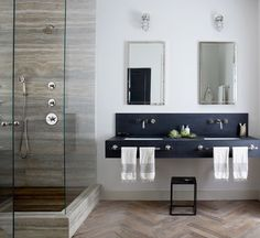 New York City–based designer Jenny Wolf  used mirrors and patterns for this windowless bathroom. Tall mirrored medicine cabinets and a glass shower amplify light from the interior fixtures, brightening up the space. Wolf used built-in cabinets to save floor space. A herringbone wood floor gives the illusion of a larger and warmer bath.