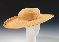 Straw picture hat, by Caroline Reboux, French, ca. 1910. As a counterpoint to the slender body silhouette of the period 1906-1913, hats expanded, often to enormous size, reaching their maximum circumference of two yards in 1911. Despite the full, wide hairstyles worn at the time, hats of this size required an interior bandeau to support the oversize crown on the head.