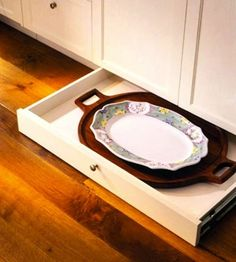 Cooking accessories and oversized serving dishes find a home in low, horizontal drawers slotted into the barely visible inches between kitchen cabinets and the floor surface.