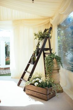 Need something beautiful to fill an empty corner of your backyard tent? Create a pretty garden-themed setup using a vintage ladder and greenery.