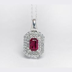 14 Karat White Gold, Ruby And Diamond Pendant Consisting Of A Center Emerald Cut Natural Red Ruby Weighing = 0.75ct, Accented By Two Rows Of Diamond Halos, Containing 44 Round Diamonds Weighing = 0.26ct Total. Pendant Includes With A White Gold Chain