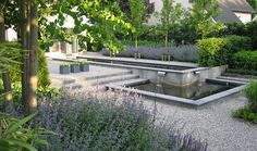 water feature as part of a larger garden-simple contemporary design, minimal colour but interesting combinations of plants by Rodenburg Tuinen