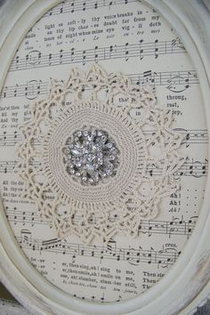 This shabby white lace collage is made up everything vintage, and would be perfect for anyone who loves the fresh clean look of rhinestones, shabby white, old sheet music and vintage lace. The ornate, wooden oval frame has been distressed and painted white, with just a touch of soft gold to show the details. Vintage sheet music is the background, then an antique, delicate lace piece and finally the centerpiece of an ornate and aged rhinestone to set it off. Would look stunning in a grouping…