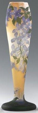 Emile GALLE (1946-1904), vase en verre multicouche à décor d'une hampe à décor de clématites en mauve et vert sur fond orangé. Signé. Hauteur : 41 cm.