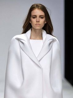 - white, armless jacket with clean silhouette, smooth lines and moulded, sculptural collar detail // Tze Goh