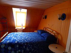 La chambre lambrissée comporte un lit double en fini laiton, un coin travail devant la lucarne. Le plancher d'origine a été dégagé ici. L'éclairage d'ambiance est appuyé d'un éclairage d'appoint pour travailler ou lire au lit. www.bleulumignon.ca