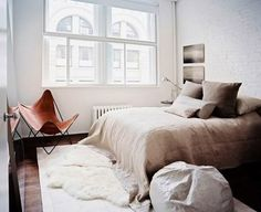 natural hues in the bedroom. layered rugs. leather butterfly chair.