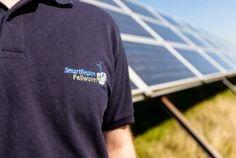 Ein Solarfeld, davor ein Mann mit T-Shirt, auf dem SmartRegion Pellworm steht