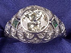 Art Deco Platinum, Diamond, and Emerald Ring, bezel-set with an old European-cut diamond weighing approx. 1.58 cts., two emerald highlights, further bead-set with old single-cut diamond melee, foliate engraved shoulders and millegrain accents