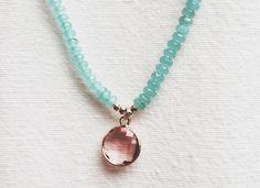Colgante piedras naturales azules con piedra de cristal engarzada color rosado unido a la mitad con cordón. - lascosasdecoco.es
