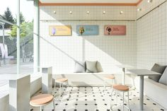 The retail space is a modern translation of retro ice cream parlors. Elements such as glowing light bulbs, painted wood paneling, black-and-white checkered mosaic tiles, and vintage ceiling fans are reminiscent of the past and arouse nostalgia.