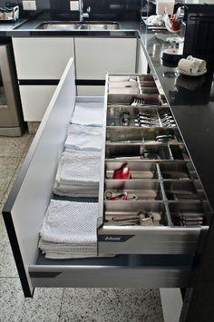 Os armários possuem gavetas dentro de gavetas: são acessórios que ajudam a separar talheres e outros utensílios e aproveitam melhor a altura do armazenador. As ferragens usadas são da Blum.  Fotografia: Divulgação.