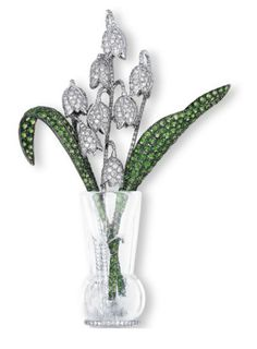 A DIAMOND, GARNET AND CRYSTAL BROOCH, BY MICHELE DELLA VALLE. Designed as a bouquet of pavé-set diamond lily of the valley flowers, accented by tsavorite garnet leaves, to the rock crystal vase, mounted in 18k white gold, 8.4 cm long, in a silk Michele Della Valle case