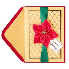 Presented as if it were a beautifully wrapped present, this holiday card features a stunning poinsettia made of red satin ribbon topped with a gold bead center.