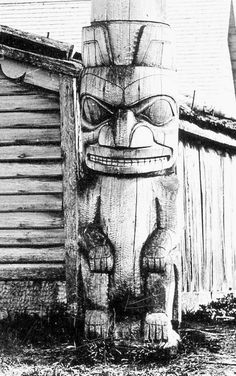A memorial pole with a separately carved bear at the top of a stack of five cylinders, and at the base, a grizzly bear.