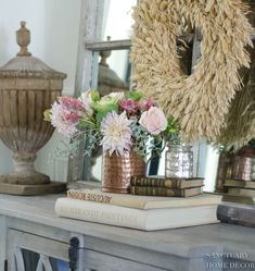 On my living room console, I stacked linen covered books first and then added smaller leather bound styles. Soft pink and green flowers in a hammered copper pitcher say fall without being too much. A simple mercury glass candle adds a touch of brightness and a simple wheat wreath, layered in the background finishes the look. French Country Decorating, Fall Decorating, Decorating Your Home, Country French, Modern Farmhouse Design, Farmhouse Decor, Farmhouse Style, Glass Kitchen Cabinets, Seasonal Decor