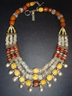 Designed by Luda Hunter   Necklace.  A triple strand antique trade beads including Venetian yellow fancies, antique carnelian, Afghan rock crystal melons, white african glass trade beads, Madura amber from Java, Ethiopian coin silver drop pendants and Naga brass beads.  9.25 sterling silver clasp.
