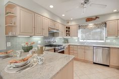 Beach house kitchen with Crema Astoria granite countertops and a gray subway tile backsplash.  Kitchen by Stoneshop from Cherry Hill, NJ.