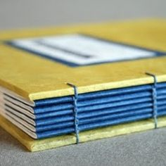 A custom, handbound wedding guest book made with eco-friendly materials and bright, sunny colors.