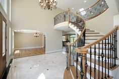Foyer with view of upper-level landing reached by slightly arched stairs