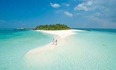 Where can you walk on the white sand beach with calm green water around you? Maldives. http://www.theguardian.com/travel/2013/mar/03/the-maldives-beach-holiday-on-the-cheap