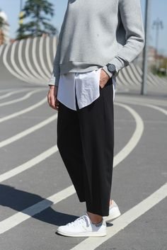 Super stylish minimalist street outfit: grey sweater, white shirt, black loose pants and white sneakers.