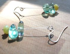 "Faceted Limey-Yellow Chalcedony and Aqua Blue Fluorite are Stacked Together on a Sterling Silver Wire. Sweet & Delicate...Perfect for your Favorite Beach Outfit!    Sterling Silver French Hooks  Rubber Earring Backs Included with Earrings, Not Shown in Photos  Length is Approximately 1.5"".      $16.00"