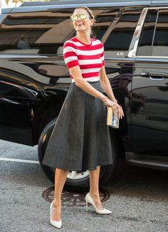 Helena Bordon com saia midi e blusa com listras vermelha.