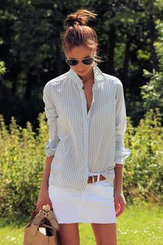 Casual button up long sleeve, partially tucked into a cute white denim raw edge short skirt.