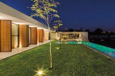 Os quartos e a área gourmet vislumbram a piscina com raia, revestida com pedras da Indonésia. O fechamento dos ambientes foi feito com portas de vidro e muxarabis