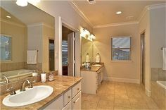 Spa inspired bathroom with tile flooring, his / her vanities, crown molding and a separate tub / shower.