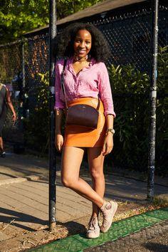 Look colorido no festival Afropunk com saia laranja e camisa rosa. Tenis Converse All Star de cano alto.