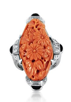A carved coral, diamond, enamel and platinum ring, circa 1925.