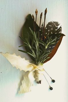 3 sprigs of a hearty stemmed herb, such as rosemary, as used here, lavender, thyme, etc.  - 2-3 small/baby magnolia leaves  - 4-6 birch branch tips, or curly willow tips or any small twig tips found outside!  - 2 pins  - ½ yard of vintage ribbon  - Guinea feather  - Scissors  - Floral tape